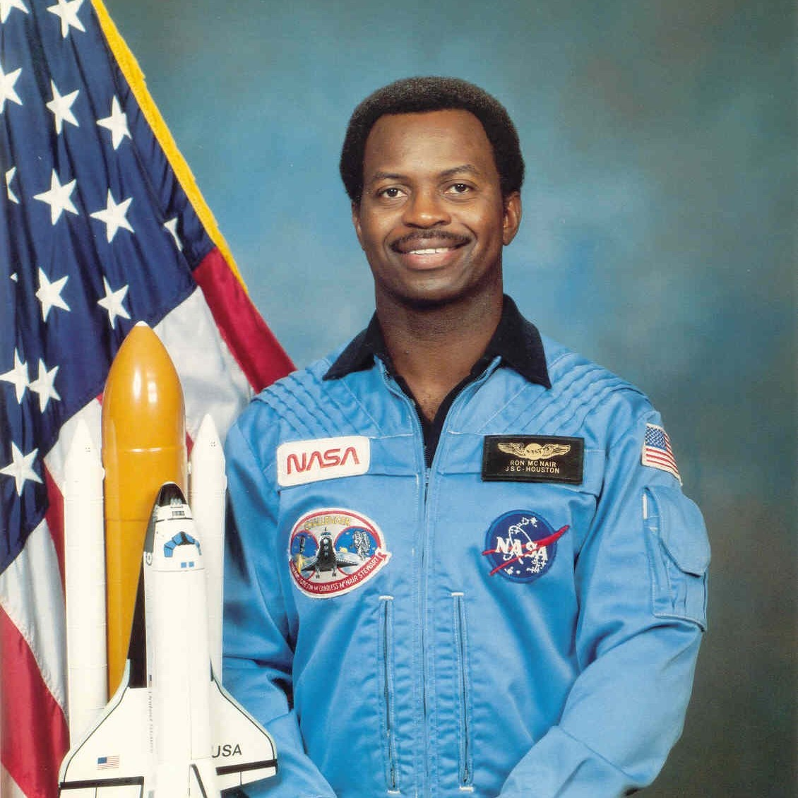 Ronald E. McNair in NASA flight suit standing with a USA flag and model of the space shuttle.